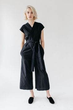 Our bestselling style is now available year round! Easy to wear wrap jumpsuit with flattering v neck front. Opening in one side allows the attached ties to slip through and wrap around the body. Wide leg skims ankle, in seam pockets at hips. The denim and black linen/cotton jumpsuit features a raw edge pant hem that frays a little with each wash. A three thread cover stitch near the edge holds the fray in place. Available in 8oz dark wash denim, 7oz black organic linen/cotton, or ligh...