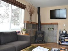 I also like just the chunky wood beam shelf above the tile. Home Fireplace, Corner Wood Stove, Wood Pellet Stoves, Home, Family Room, Wood Burning Stove Corner, Standing Fireplace, Tiny Living Rooms, Corner Fireplace