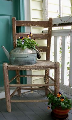 Wooden Chair and Aluminum Tea Kettle... no one wanted these, so I nabbed them for one dollar each at a country auction! Wired the lid to hang from the handle of the tea kettle, added some spring-y violas to finish - I think this looks great on my porch!