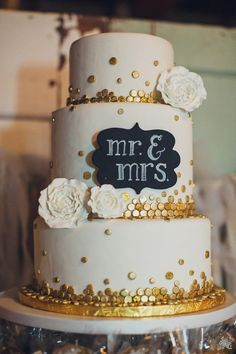 white wedding cake with glittering gold discs and chalkboard topper
