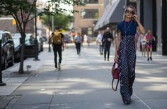Natalie Joos wears a mixed floral print jumpsuit with a red satchel and round sunglasses