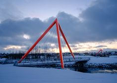 A pair of hollow red pyramids support the weight of these bridges that span the mouth of the river Elliðaár