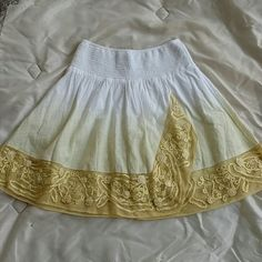 Divine Free People Mini Skirt This divine skirt from Free People is new with tags! Elastic waist with white and pale yellow ombre design. Beautiful embroidered golden stitching detail against sheer nylon fabric at bottom with built in liner. Size XS.  Elastic waist measures 11.5 inches across with plenty of stretch. Measures 16.5 inches in length. Gorgeous! Free People Skirts Mini