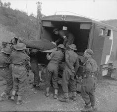 A casualty being loaded into a motor ambulance at Ortona, Italy in December 1943. The patient will then be taken to an Advanced Dressed Station (ADS).