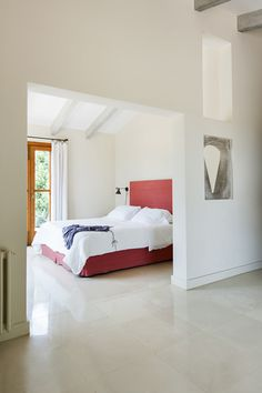 A pink upholstered headboard dresses up clean white linens.  Click through for the full tour of this tranquil home in Majorca.