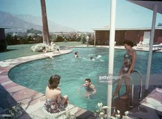 Female and male guests relax near and swim in the piano-shaped swimming pool at Twin Palms, the estate belonging to American singer and actor Frank Sinatra (1915 - 1998), Palm Springs, California, 1951. A woman cautiously tests the water with her foot as people swim nearby or sunbath along the sides of the pool. Designed for Sinatra in 1947 by Architect E. Stewart Williams, Sinatra and his second wife Ava Gardner lived in Twin Palms until the couple divorced in 1957 and Sinatra moved to…