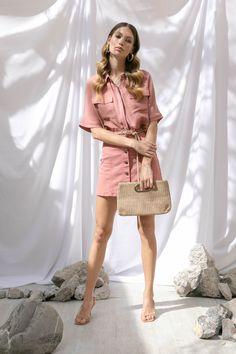 Camisa manga corta con bolsos rosa, cinturón trenzado y arracadas doradas MAP, Falda denim rosa y clutch de fibras naturales That's It, sandalias beige Kurt Geiger.