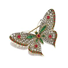 DIAMOND, EMERALD AND RUBY BUTTERFLY BROOCH Mounted en tremblant, set with round, cushion-shaped and fancy shaped emeralds and rubies, further set with numerous old-mine and single-cut diamonds weighing approximately 9.75 carats, mounted in gold and silver.