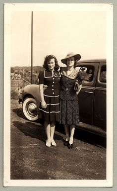 Two women dressed in the fashion of the 1940s with a Ford De Luxe.