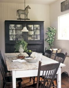 Prim Country Farmhouse Dining...white chippy table & old painted black chairs and cupboard.