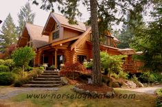 Wish I could landscape this well... brings out the natural beauty of the handcrafted log home!