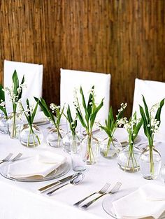 simple lily of the valley flowers in bud vases
