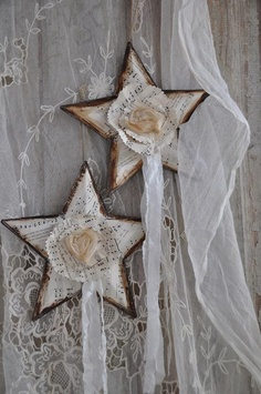 Metal stars from Dollar Store - repainted with several coats before covring with sheet music, flowers, paper and sheer streamers - posted by Counting Your Blessings