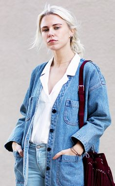 Courtney Trop of Always Judging wears a button-down blouse, denim jacket, jeans, and a burgundy fringe bag