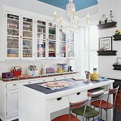 Can I get some craft room love right here.  Blue ceiling, chandelier, glass doors, organization....  Joy!