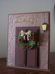 SueBee Cards Susan Bagley Christmas Door wishing you Blessings. Sizzix brick EF, Punch bunch pine branch MINI, hand made door and knob, light made from small price tag punch,mini flower punch, glossed with glossy accents, stickles, wired ribbon. - bjl