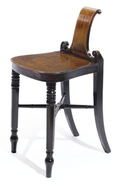 A Regency mahogany hall stool circa 1810 The backscrolled backrest above a plank seat, raised on reeded legs joined by stretchers. height 30 1/2 in.