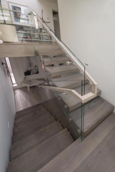 The stunning staircase serves as a focal point in this dynamic home. Open risers and a transparent glass balustrade make the staircase look and feel as if it's floating. Outdoor Stair Railing, Porch Stairs, Concrete Staircase, Staircase Handrail, Glass Stairs, Wood Stairs, Floating Stairs, Glass Stair Railing, Glass Balustrade
