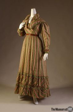 """1820-1822 Dress of multicolor cotton and green wool braid, England, FIT Collection  """"By the 1820s, multicolor, patterned garments had begun to replace the gossamer white of the century's first decade, due in large part to new developments in printing technology. Textile manufacturers were able to mechanize and economize production using engraved rollers rather than traditional wood blocks or copper plates."""""""