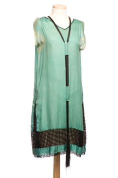 Green silk shift, 1920s, with a black ribbon lattice panel down the center back, around the lower skirt and in triangular pleats on the sides. Charleston Museum