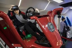 A Chinese woman takes her virtual reality (VR) glasses off while riding a high speed car racing simulator at Leke VR Park, a leading chain, on November 26, 2016 in Beijing, China. While virtual reality is still seen as a niche technology in many Western countries, VR is flourishing in China as a form of mainstream entertainment. Hundreds of VR arcades, kiosks, cafes, and 'experience rooms' are springing up in cities across the country, and offer a VR experience for about the price of a movie…