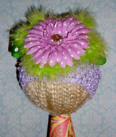 "Light purple waffle hat with light purple polka dot flower, green polka dot ""leaves"" and green feather embellishment."
