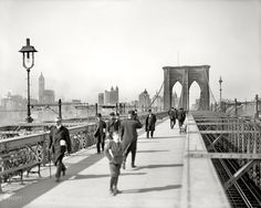 New York circa 1907. 'Brooklyn Bridge.' At left, the Singer Building under construction.