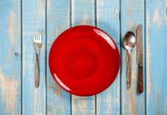 #Empty red plate  Empty red plate on blue wooden table with knife spoon and fork