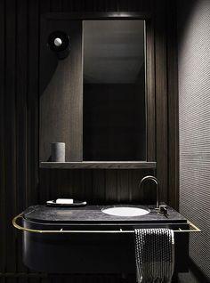 Moderne Badezimmer mit dunklen Holzplatten, eine schwarze Marmortheke und einen großen Spiegel