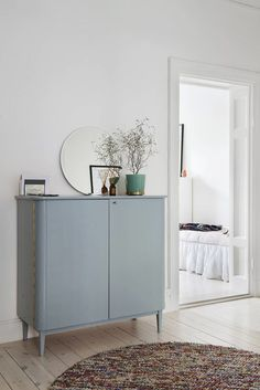 Vintage look pale blue hallway cabinet and bare walls/floors