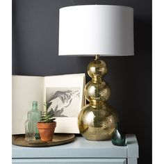 Create a look that will surely sparkle within any space with this eye-catching table lamp. Featuring a gold mercury glass stacked gourd base with an ivory faux silk shade, this piece will cover your space in trend worthy charm.