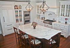 Massive marble-topped dark wood island dominates this kitchen, replete with white detailed cabinet surfaces, brushed aluminum appliances, and natural wood flooring.