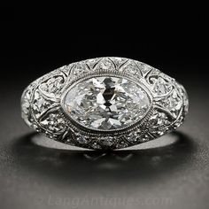 A dazzling dream ring - circa 1910-1920. An icy white, high-clarity  moval diamond (an elongated oval or rounded tipped marquise), weighing 1.63 carats and bearing a GIA Diamond Grading Report stating: E color - VS1 clarity, sparkles mightily from within its original home - an exquisite platinum and diamond Edwardian/early-Art Deco mounting. The ring is delicately adorned with decorative openwork details, both scrolled and geometric, and twinkles on all sides with an array of tiny single...