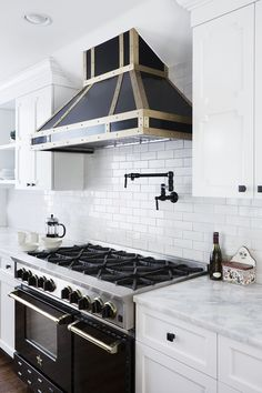 French Contemporary Traditional Kitchen: A dramatic black-and-gold range and hood with a pot filler in a contemporary white kitchen.