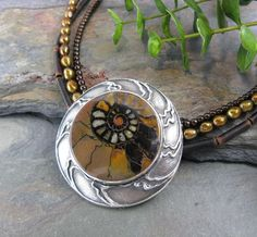Ammonite Circle Pendant by Lisa Barth  Bezel set ammonite cab in a fine silver clay setting made using a photopolymer plate made by the artist.