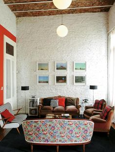 brown couch, floral couch, brick walls, chairs, ceiling, pictures, brown chairs
