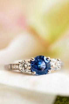 A beautiful sapphire three stone engagement ring with pavé-set diamond accents.==