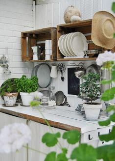 White paint, green plants, wooden crates for this rustic outdoor kitchen.