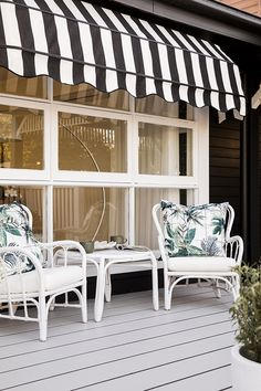 A balcony with a view. Black and white window coverings with greenery on outdoor furniture.
