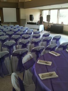 Our white tablecloths with white folding chair covers. Our organza purple overlays with purple organza chair sashes.