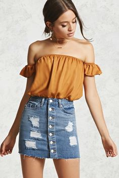 A denim skirt featuring front whiskering, distressed details, a button-down front, a five-pocket construction, and a frayed hem.