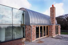 The modern extension to a farmhouse plays with blended red brick, glass and a curved lead roof