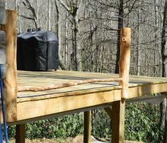 Rustic deck construction - natural logs for railings (from Lise's Log Cabin Life: Building A Rustic Deck Railing, Part 2)