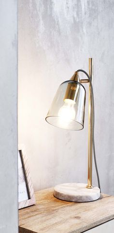 Light up living spaces with the high shine finish of the Glass Shade Marble Table Lamp.