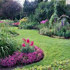 A rippling flowerbed dresses up a garden. Undulating curves create a gentle edge to both the border and the beds in this garden. In place of a hardscape material, a stretch of lawn serves as walkway. A castor bean adds vertical height to the flowerbed. Repeating plants, including delphinium and phlox, supply visual consistency. Annuals such as snapdragons add welcome bursts of bright color.