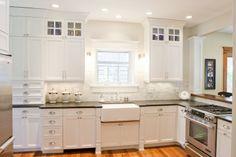 White cabinets, slide in stove, wood bar, dark counters, marble tile: Ashton Home - Benjamin Blackwelder Cabinetry