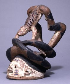 Yoruba gelede mask  - Register 1942: Wooden mask carved in form of human head, painted white, black, brown and blue, with slits for seeing through, surmounted by two large snakes eating the hind legs of a leopard.