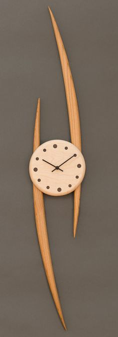 Artist-made wooden wall clock is created from black walnut and maple. Slope Clock created by artist Steve Uren.