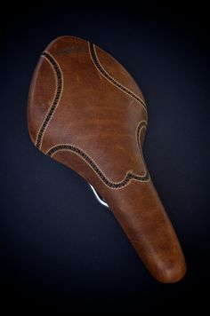 LASER CUT WINGTIP LEATHER ARIONE SADDLE This is the updated laser cut Fizik Arione saddle with the classic brogue wingtip design. Shown in Antique brown with Smoke and Old Gold stitching.