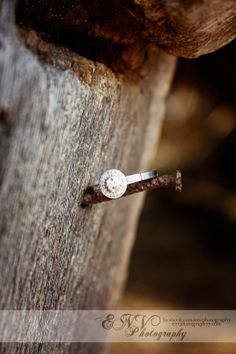 country couple engagement pictures with ring on an old barn nail. <3